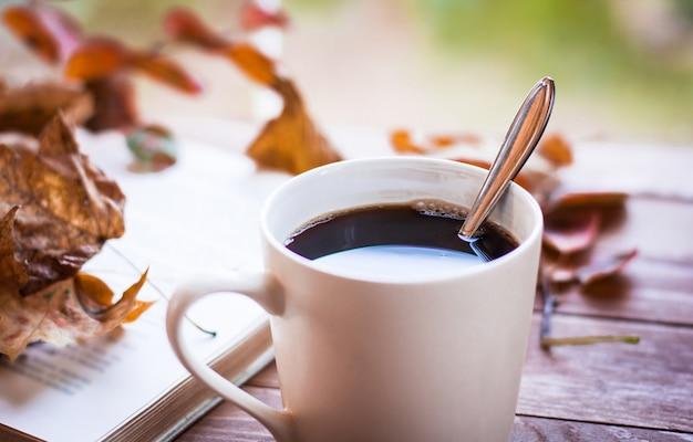 Kubek gorącej, parującej kawy i starej książki na drewnianym stole