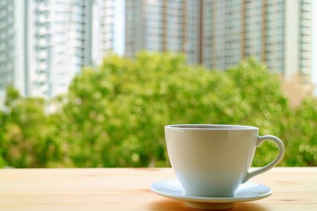 Kubek gorących napojów na drewnianym stoliku przy oknie z rozmazanymi zielonymi liśćmi i wysokimi budynkami