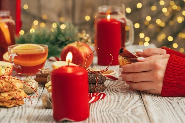 Kubek grzanego wina w rękach kobiety na drewnianym stole