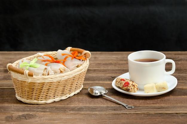 Kubek herbaty, batoników musli i sitka do herbaty. wiklinowy kosz z prętami. brązowy drewniany