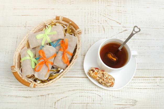 Kubek herbaty i batonu musli. wiklinowy kosz z prętami