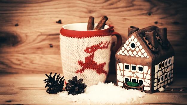 Kubek herbaty lub kawy. prezent z czerwoną wstążką i . słodycze i pikantność. ozdoby świąteczne. drewniane tło.