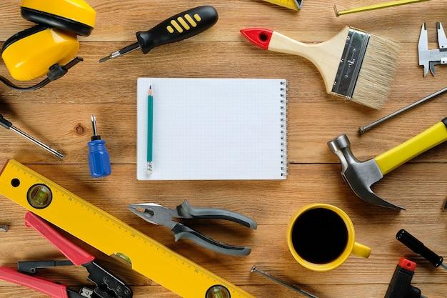 Kubek herbaty lub kawy, rysunki i narzędzia budowlane do profesjonalnej konstrukcji lub napraw domowych, na drewnianym stole