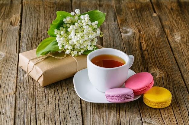 Kubek herbaty z bukietem kwiatów konwalii
