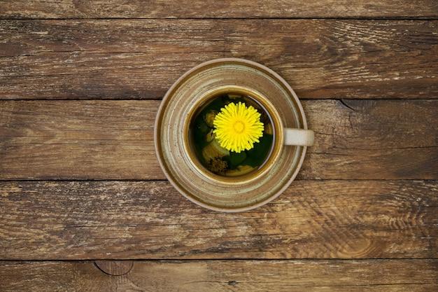 Kubek herbaty z mniszka lekarskiego ze świeżymi kwiatami ziołolecznictwo napój witaminowy