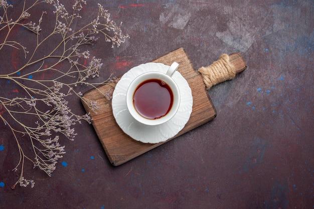Kubek herbaty z widokiem z góry wewnątrz szklanego kubka z talerzem na ciemnej przestrzeni