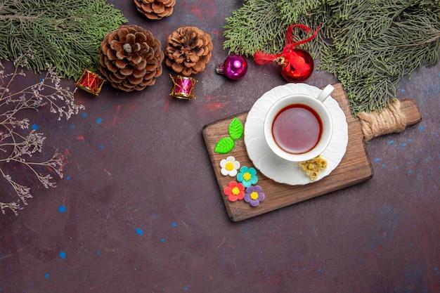 Kubek herbaty z widokiem z góry z szyszkami na ciemnej przestrzeni