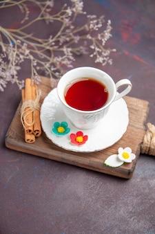 Kubek herbaty z widokiem z przodu wewnątrz szklanego kubka z talerzem na ciemnej przestrzeni
