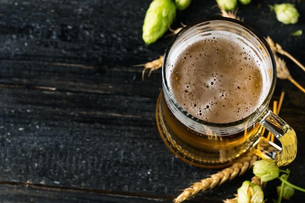 Kubek jasnego piwa na ciemnym tle z zielonymi chmielami i kłosami pszenicy