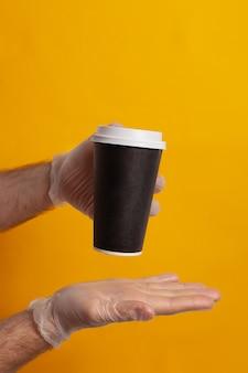 Kubek jednorazowy trzymany w dłoni w rękawicy ochronnej