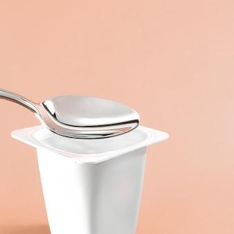 Kubek jogurtowy i srebrna łyżka na beżowym tle biały plastikowy pojemnik z kremem jogurtowym świeży produkt mleczny dla zdrowej diety i równowagi żywieniowej