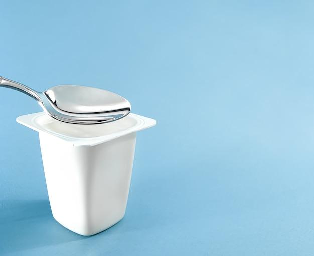 Kubek jogurtowy i srebrna łyżka na niebieskim tle biały plastikowy pojemnik świeży produkt mleczny dla zdrowej diety i odżywiania