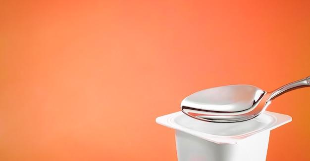 Kubek jogurtowy i srebrna łyżka na pomarańczowym tle biały plastikowy pojemnik z kremem jogurtowym świeży produkt mleczny dla zdrowej diety i równowagi żywieniowej