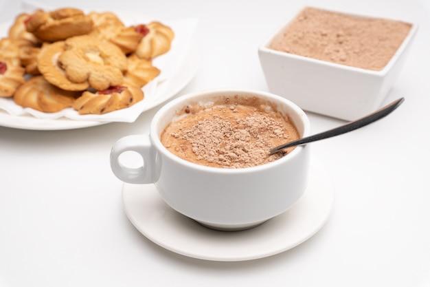 Kubek kakao z grudkami z pastami i kakao w proszku na białym tle