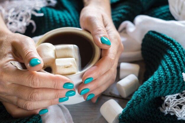 Kubek kakao z pianką marshmallow w kobiecych rękach z niebieskim manicure