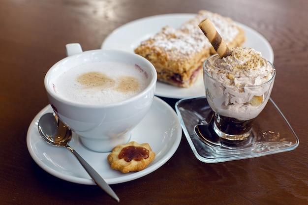 Kubek kawy i deser stojący na drewnianym stole brązowy