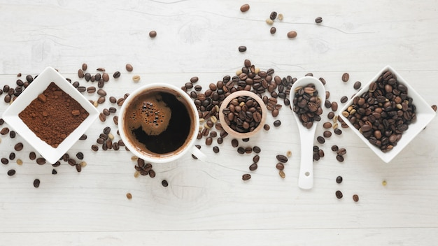 Kubek kawy; kawa w proszku i ziarna kawy ułożone w rzędzie na biurku