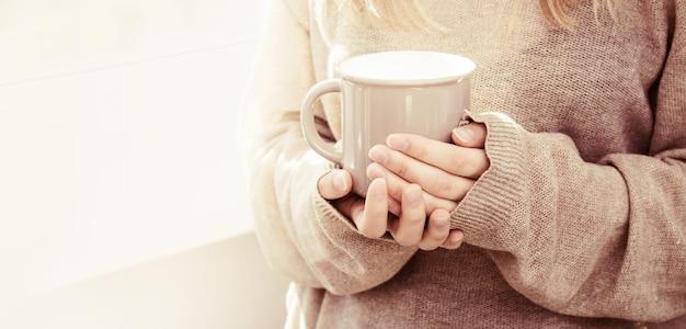 Kubek kawy w rękach kobiet z dzianinowym swetrem