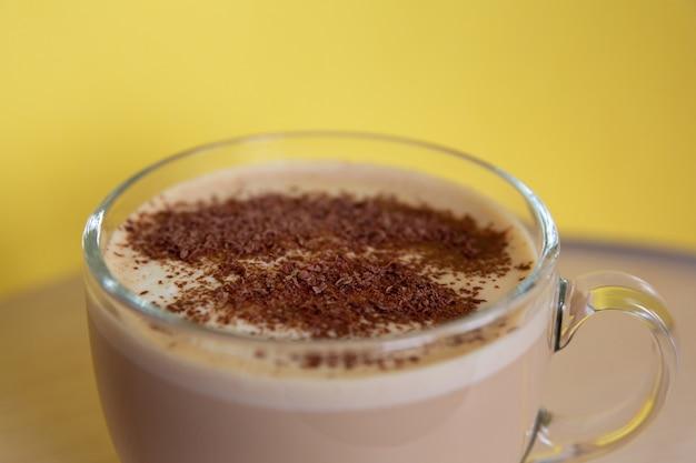 Kubek kawy z mlekiem posypany kawałkami czekolady i pianką radość energii o poranku