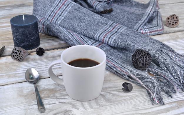 Kubek kawy z szalikiem i świecą na stole