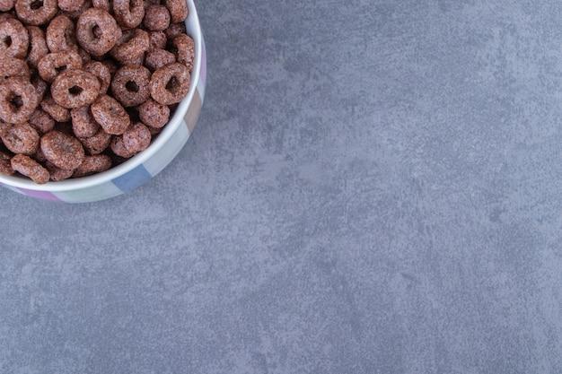 Kubek krążków kukurydzy na niebieskim stole.