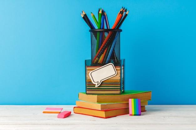 Kubek kredek i stos książek na stole