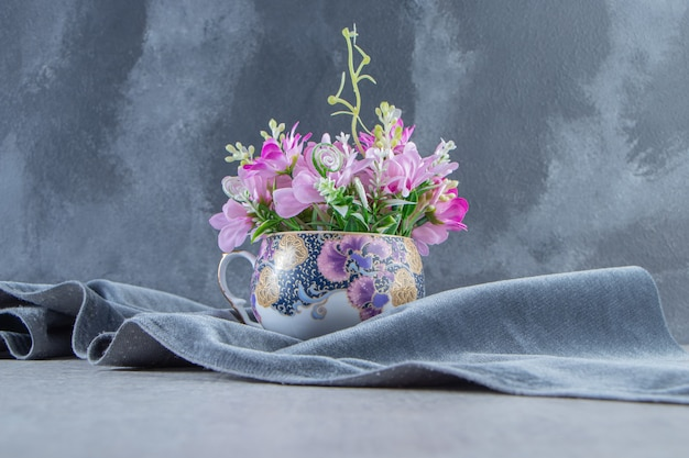 Kubek kwiatów na kawałku materiału, na białym stole.
