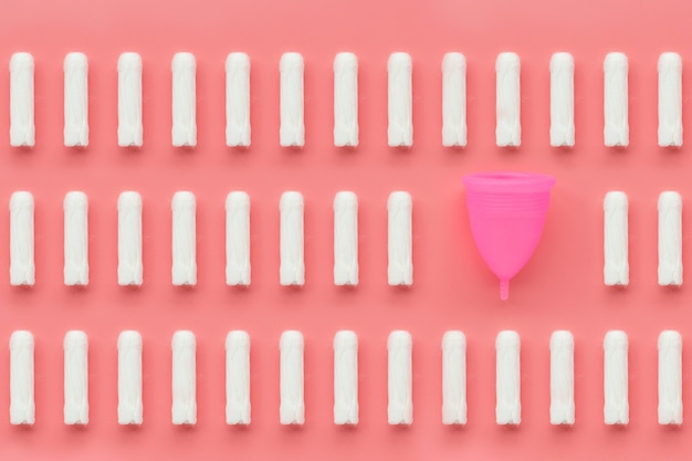 Kubek menstruacyjny i tampony na różowym tle