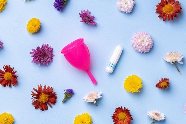 Kubek menstruacyjny i tampony na widok z góry tło kwiatowy wzór