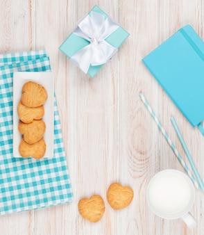 Kubek mleka, ciasteczka w kształcie serca i pudełko na białym drewnianym stole z miejscem na kopię