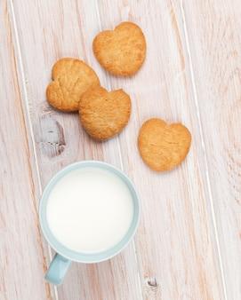 Kubek mleka i ciasteczka w kształcie serca na białym drewnianym stole