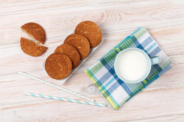 Kubek mleka i ciastek na białym drewnianym stole