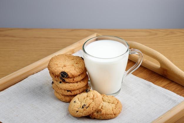 Kubek mleka i ciastek z rodzynkami na drewnianej tacy