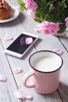 Kubek mleka, telefon i dogrose na białym drewnianym stole
