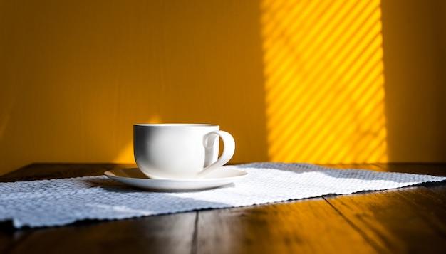 Kubek na drewnianym stole w porannym słońcu