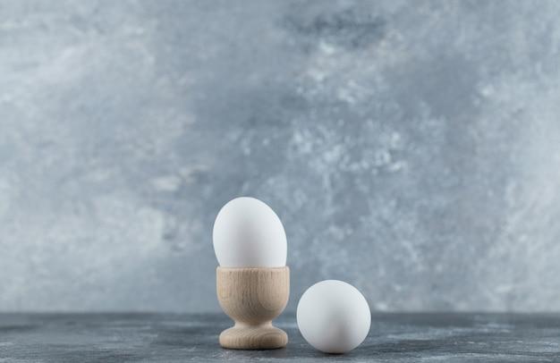 Kubek na jajka i jajka na szarym stole.