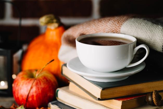Kubek na stosu książek jesienią