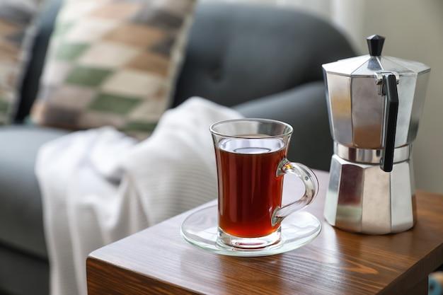 Kubek napoju i dzbanek do kawy na stole w podłokietniku w pokoju