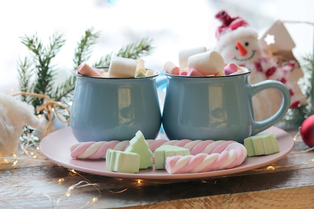 Kubek napoju z piankami iluminacjami świątecznych dekoracji na drewnianym parapecie