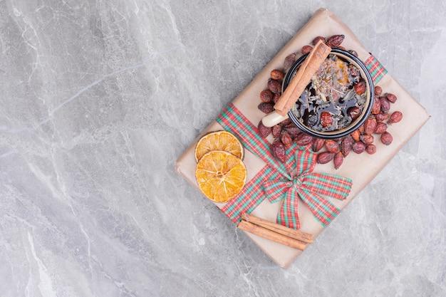 Kubek napoju z ziołami, przyprawami, cynamonem i pomarańczą.