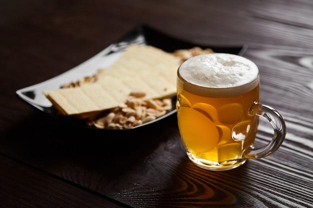 Kubek niefiltrowanego jasnego piwa pszenicznego z piwnymi przekąskami na drewnianym stole