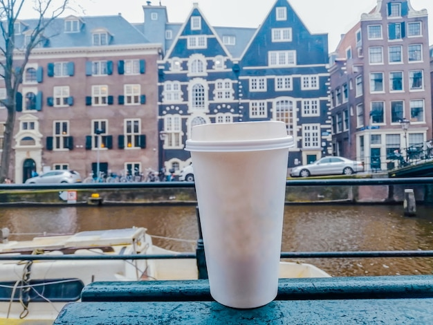 Kubek papierowy biały na gorące napoje na tle architektury amsterdamu. fotografia napojów.