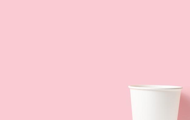 Kubek papierowy biały na różowym tle. widok z góry. miejsce na tekst. koncepcja ekologii