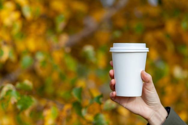 Kubek papierowy biały z kawą w ręce kobiety. czas na kawę w mieście. kawa na wynos. ciesz się chwilą, zrób sobie przerwę. jednorazowy papierowy kubek zbliżenie. pyszny gorący napój. puste miejsce na tekst, makieta
