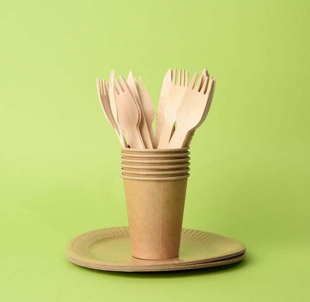Kubek papierowy brązowy, talerze na zielonym tle. koncepcja odrzucenia tworzyw sztucznych, zero odpadów, z bliska