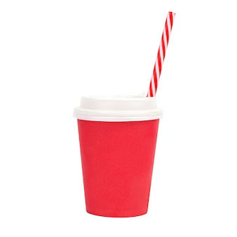 Kubek papierowy czerwony z czerwoną słomką na białej ścianie na białym tle.