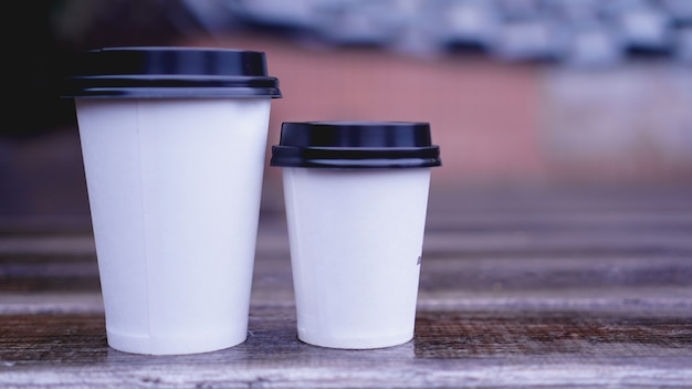 Kubek papierowy do kawy stoi na powierzchni drewnianych na niewyraźne tło. miejsce na tekst lub logo.