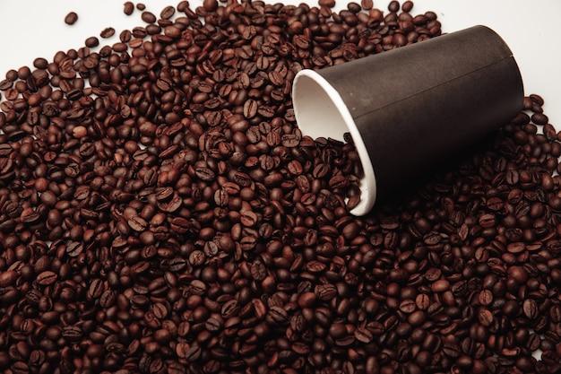 Kubek papierowy do kawy z ziarnami kawy na białym tle