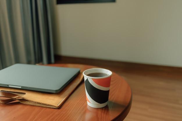 Kubek papierowy gorący napój i laptop na stole. koncepcja pracy w domu.