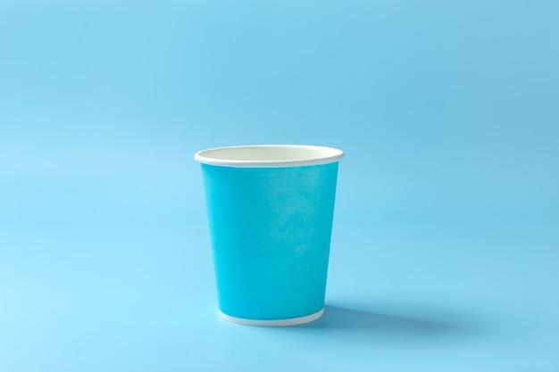 Kubek papierowy jednorazowy na jasnoniebieskim tle.